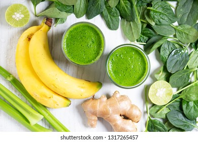 Fresh green smoothie with spinach, banana and ginger on wooden background
