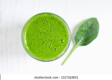 Fresh green smoothie with spinach on wooden background
