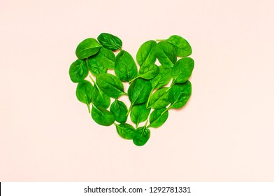 Fresh green spinach leaves in the shape of heart on pink background Flat lay top view copy space. Creative food concept. Ingredient for salad. Vegetable design. Healthy lifestyle