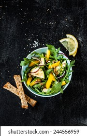 Fresh green spring salad with arugula (rucola), yellow pepper, zucchini, sunflower seeds and croutons on black chalkboard background from above. Poster layout with free text space.