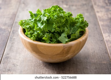Fresh green superfood kale leaves in wooden bowl on wooden background
