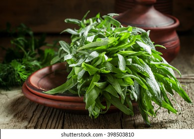 Fresh green tarragon in a beam in an earthenware pot on the old wooden background in rustic style, selective focus