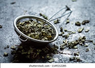 Fresh green tea in old metal strainer on black table