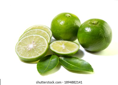 Fresh green Thai lemons, whole and sliced with their leaves, placed on a isolated white background. With copy space.