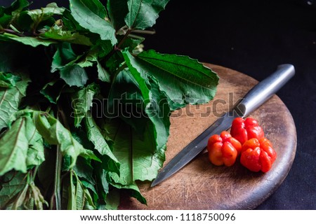Fresh green vegetable spinach pumpkin leaves or Nigerian Ugwu on vintage wooden chopping board with knife and red chilli pepper isolated on dark background for rustic cooking concept for local Market