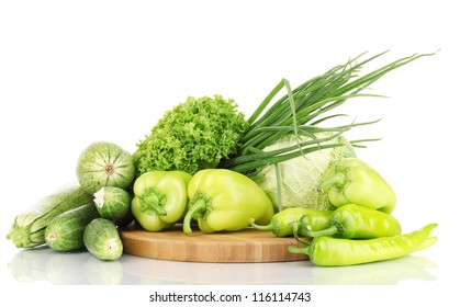 fresh green vegetables on chopping board isolated on white