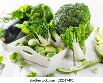 Fresh green vegetables on  white wooden table. Selective focus