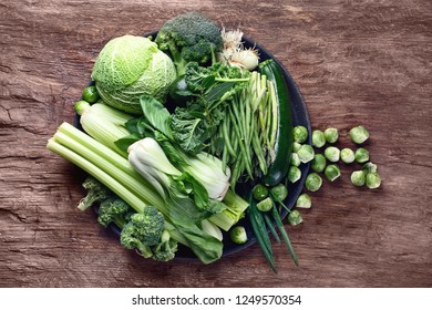 Fresh green vegetables on wooden table. Top view. Flat lay