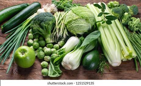 Fresh green vegetables on wooden table.