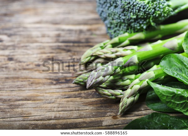 Fresh green vegetables on wooden background with copy space