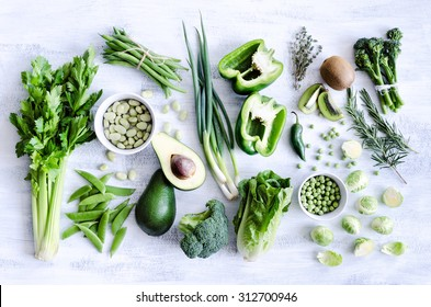 Fresh green vegetables variety on rustic white background from overhead, broccoli, celery, avocado, brussel sprouts, kiwi, pepper, peas, beans, lettuce,