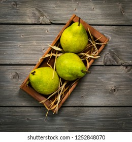 Fresh Green Williams Pears or Bartlett Pears on a Rustic Wooden table Top View, Autumn Concept, Low Key, Vintage Style. Selective focus.