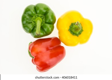 Fresh green, yellow and red bell peppers, top view, isolated on white background.