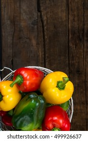 Fresh Green, Yellow, Red Bell Peppers in the Wired Basket  on Wooden Background, Space for Text