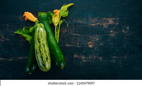 Fresh green zucchini on a black wooden table. Top view. Copy space.