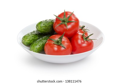 fresh greenhouse cucumbers and tomatoes in bowl, isolated on white background