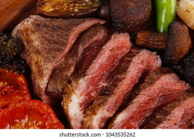 fresh grilled bbq beef meat rib eye steak on wooden plate with baked tomatoes mushroom, potatoes, hot chili pepper isolated on white backgrodun
