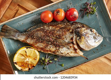 Fresh Grilled Dorado with Lemon and Cherry Tomatoes. Whole Bbq Sea Bream Fish Top View and Flat Lay. Sparus Aurata Close Up for Restaurant Menu or Recipe Illustration
