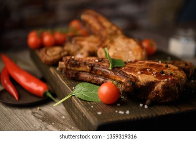 Fresh grilled meat. Grilled beef steak on a wooden cutting board with vegetables.