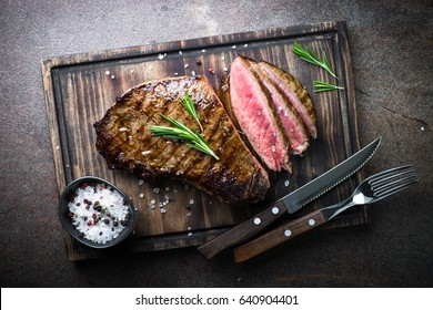 Fresh grilled meat. Grilled beef steak medium rare on wooden board. Top view.