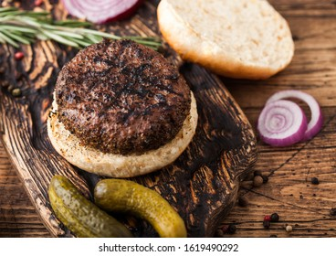 Fresh grilled minced pepper beef burger on vintage chopping board with buns onion and tomatoes on wood background. Salty pickles and fork - Shutterstock ID 1619490292