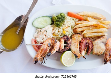 Fresh grilled mixed seafood plate with fish, shrimps, octopus and squid selective focus