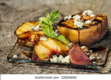 fresh grilled peaches garnished with fresh mint served with bleu cheese and a balsamic reduction on a rustic round of wood