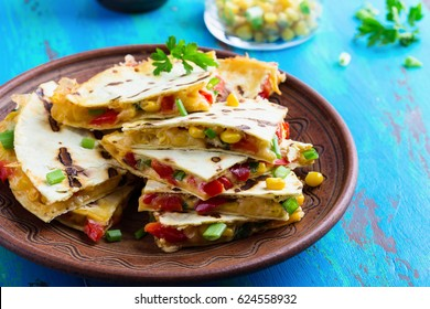Fresh grilled red bell pepper quesadillas with corn served cut into wedges on rustic table, Mexican style