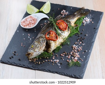 Fresh grilled sea bass with lime, condiments, tomatoes, pepper, himalayan salt and rosemary on a fancy black plate.