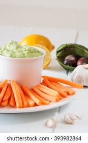 Fresh guacamole with carrot slices on a white wooden table