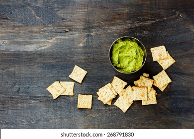 Fresh guacamole dip with chips on dark wooden background. Food and vegetarian concept. Top view.