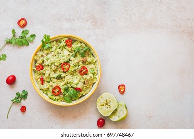 Fresh guacamole dip with ingredients on rustic stone background. Top view, lots of copy space