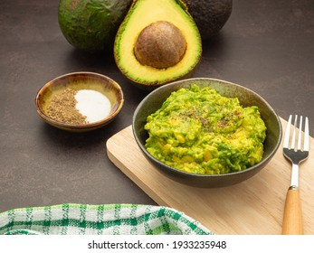 Fresh guacamole on a dish placed on a cutting wooden board with ingredients for homemade guacamole avocados, lemon, salt, and pepper. Top view.  Concept of traditional Mexican preparation.