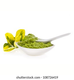 Fresh guacamole in a white bowl with a spoon isolated on white background