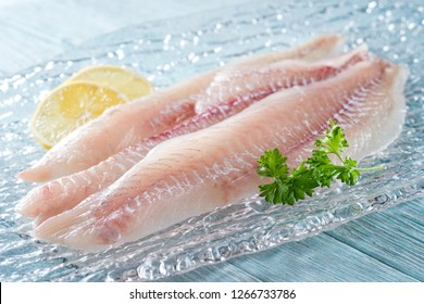 Fresh haddock fillets on glass plate with lemon and parsley.