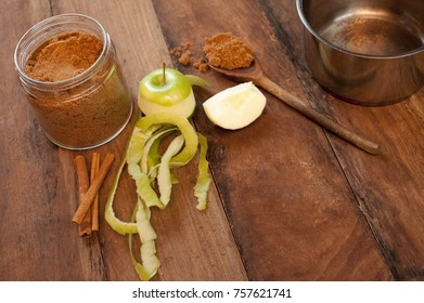 Fresh half peeled apple with aromatic cinnamon spice in the form of sticks and ground powder for use as a flavoring and seasoning in baking on a wooden kitchen table with copy space