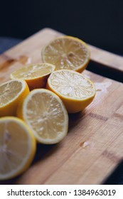 Fresh halved lemons on a cutting board. Shallow depth of field and window backlight.