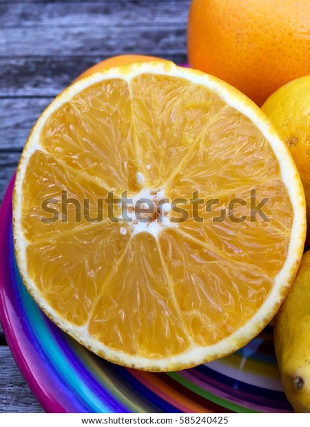 Fresh halved orange in closeup on a colorful plate