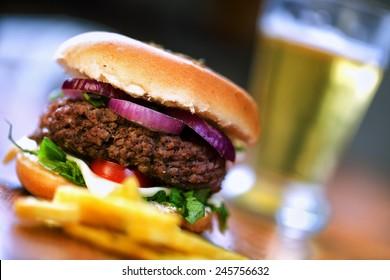 Fresh hamburger with beer and fried potatoes