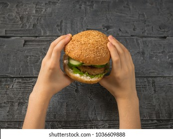 Fresh hamburger in the hands of a child over the table. Homemade food. Rustic style.