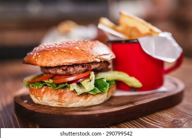 Fresh hamburger with with salad and french fries on wooden board.