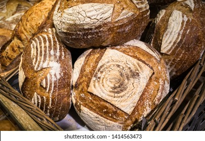 Fresh handmade artisan loafes of bread for sale on display in a basket.