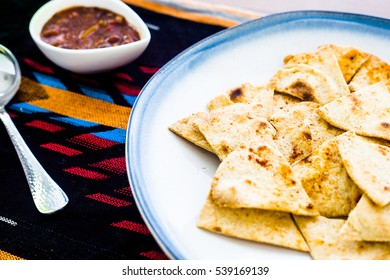 Fresh, handmade flour tortilla chips baked and served on a white ceramic plate with blue rim on Aztec patterned linen with fresh black bean and corn salsa in white rimmed cup.