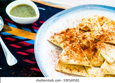Fresh, handmade flour tortilla chips baked and topped with chili powder on a white ceramic plate with blue rim on Aztec patterned linen with fresh green salsa in white rimmed cup and silver spoon.
