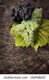 Fresh harvest of grapes. Nature theme with red grapes and yellow wooden background. Nature fruit concept.