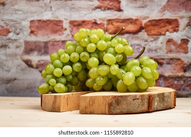 Fresh harvest of white grapes on wooden plate with brick wall background