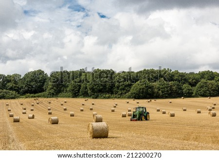 Fresh hay bales and tractor on an English field during summertime