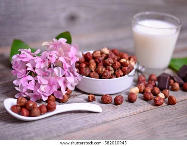 Fresh hazelnut, dark chocolate and glass of milk on wooden table