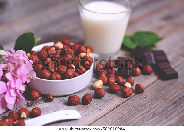Fresh hazelnut, dark chocolate and glass of milk on wooden table closeup