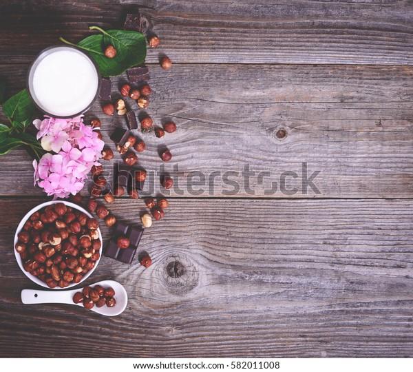 Fresh hazelnut, milk and dark chocolate on wooden table